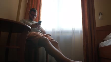 A man with glasses sits on a chair near a window in a hotel room with phone.