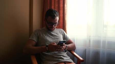 Man with glasses, red hair, watch sits on the chair and type his phone.