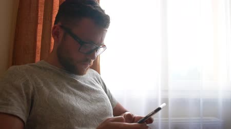 A man in glasses with a phone in his hands uses social networks - slow motion. Dostupné videozáznamy
