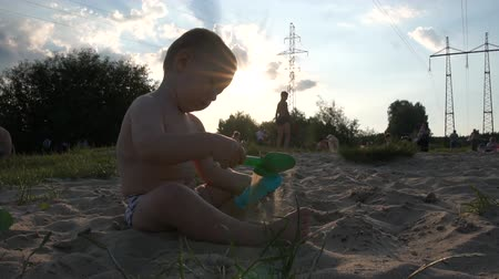 pala : City beach near power lines - Little boy sit and play with a bucket and a shovel