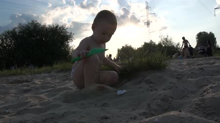 City beach - Little boy sit and play with a shovel, the action in slow motion at sunset.