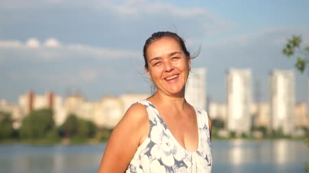 Portrait of an ordinary middle aged woman who smiles on the background of the lake. Stock mozgókép