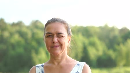 Portrait of a middle aged woman who smiles and blinks with one eye Stock mozgókép