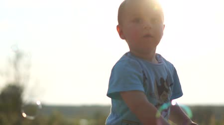 Little boy and soap bubbles at sunset in slow motion.