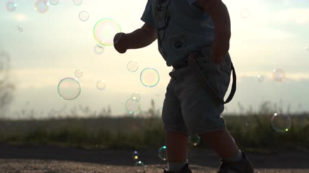 Cute Little boy and soap bubbles at sunset in slow motion Stock mozgókép