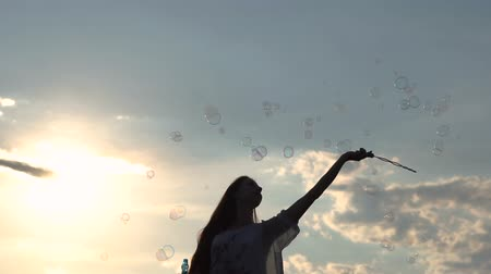 Magic wand with a lot of soap bubbles in slow motion at sunset.