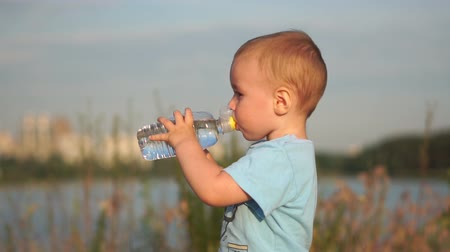 Little blond boy drinks water at sunset in slow motion.
