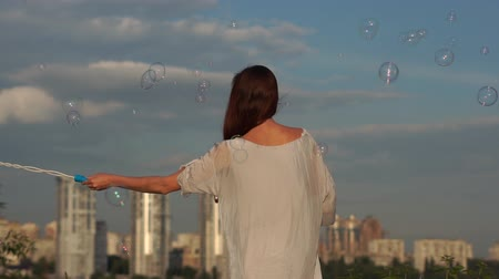 A young girl waves her hand and blows soap bubbles on the background of the city.
