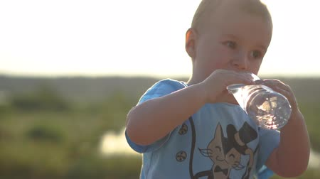 Little boy with white hair drinks water at sunset in slow motion. Dostupné videozáznamy