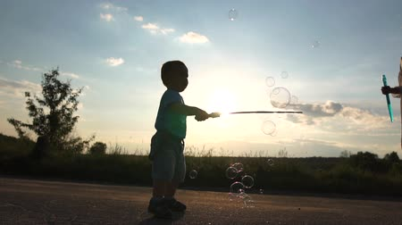 Mom and son play soap bubbles at dawn in slow motion. Stock mozgókép