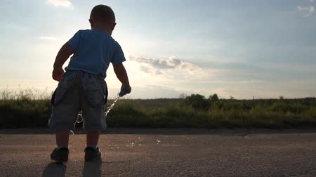 Cute Little blond boy and soap bubbles at sunset in slow motion. Stock mozgókép