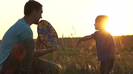 Dad holds darts in his hands and gives five to his son - slow motion, sunset.