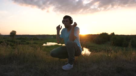 A young man listens to music in headphones and shake his head at sunset