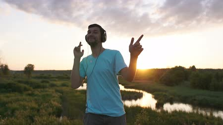 A young man listens to music in big headphones and dances at sunset near the lake