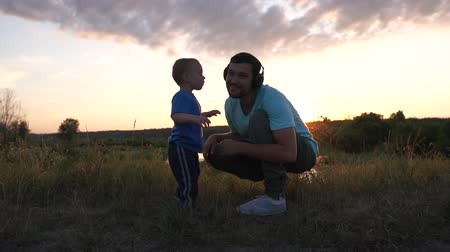 Sun kiss his father that listen music at sunset in slow motion. Stock mozgókép