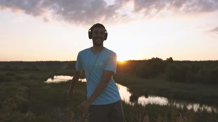 Man with headphones make pupular dance movement at sunset in slow motion.