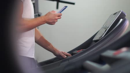 Strong man going on a treadmill and looking at smart phone in slow motion Dostupné videozáznamy