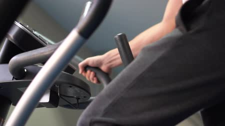 Sturdy hands holding handles of a treadmill in a fitness gym in slo-mo