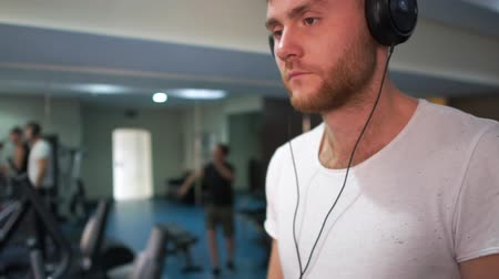 treadmill : Young bearded man in headphones going on a treadmill in gym in slo-mo Stock Footage