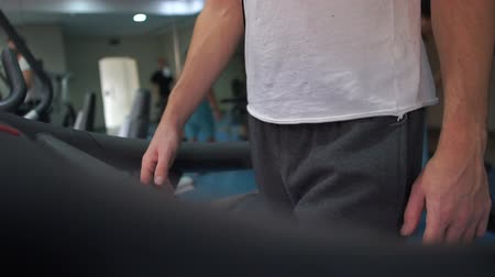 stimulating : Sportive man in a tshirt and pants walking on a treadmill in gym in slo-mo