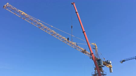 монтаж : Worker installing jib on a building crane. Industrial scene in 4k resolution