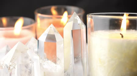 curar : Close up of quartz crystals lined and lighted color candles that flame wavers when viewed from side