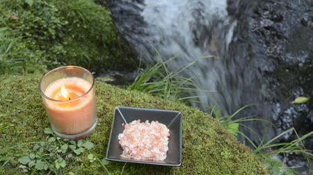 sůl : Glass candle and himalayan salt on mossy stone at riverside