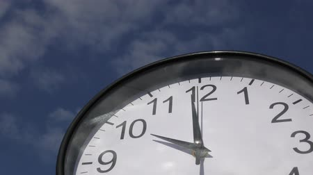minute : Black frame round wall clock under blue sky Stock Footage