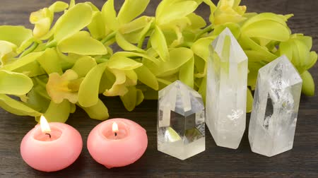 lehkost : Three quartz crystals and two pink candles in front of orchid flowers