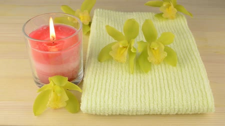 miscellaneous : Green towel and glass candle with orchid flowers on wood table