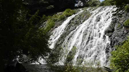Thin white waterfall falling along rugged rock slope between green forest in Kumamoto