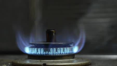 Gas stove with blue flame in front of metal wall