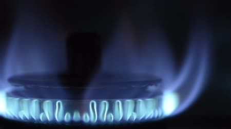 Close up gas stove with blue flame in front of dark background Stock Footage