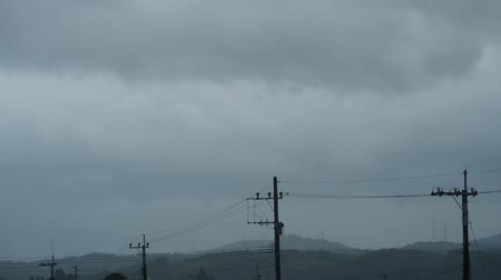 Fast flowing clouds in stormy weather above the lined electric poles