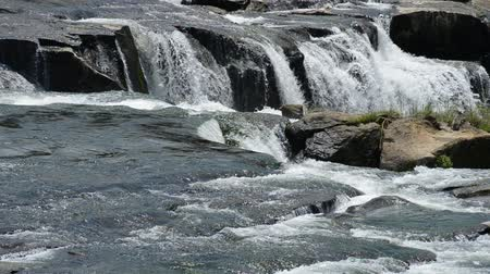 River flowing on bedrock in front of top of the waterfall