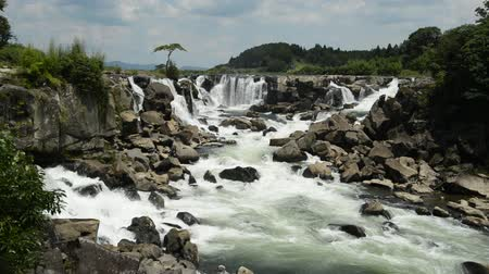 White splashing waterfall falling from several places and joins the river under blue sky 무비클립