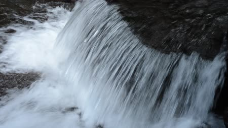 Shallow white small cascade flowing from diagonally above