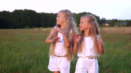 sisters : Girls catching soap bubbles. Little blond girls play with blowing bubbles. Stock Footage
