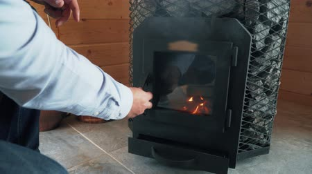 bagno di vapore : Man kindles the stove in sauna, wood stove in sauna.