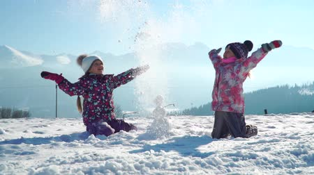 rodzeństwo : Cheerful little girls in outwear having fun and throwing snow in sunlight standing outdoors