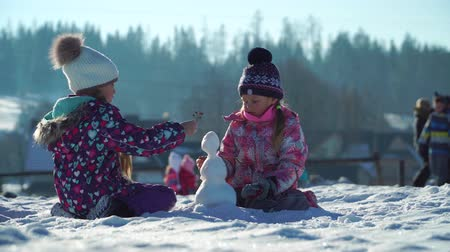 rodzeństwo : Children in outwear making small snowman while playing on snowy field in sunlight with mountains on background