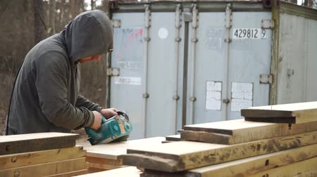 измельчение : Working man is polishing a piece of wood with a machine for grinding in the hands