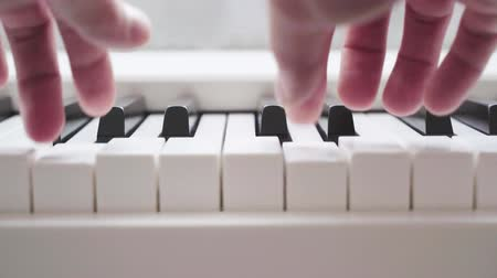 teclas de piano : tocar los dedos en el piano blanco Archivo de Video