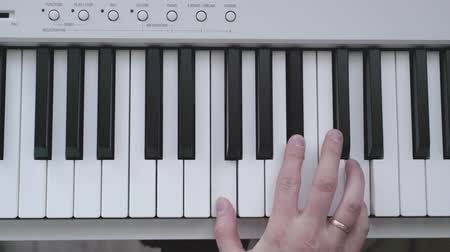fingers play on white piano
