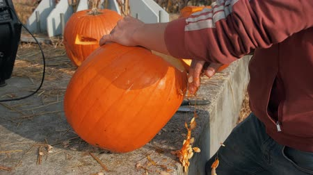 man preparing a pumpkin for halloween
