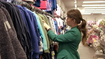 women chooses clothes for children in the shop