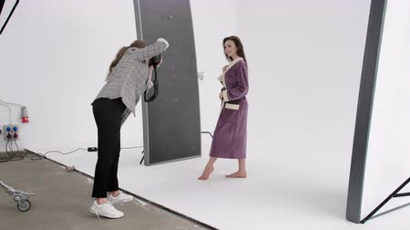 senza volto : Side view of woman with photo camera shooting barefoot lady in warm bathrobe during photoshoot in professional studio