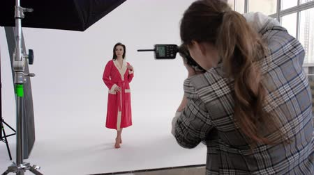 захват : Back view of woman using photo camera to shoot female model in pink bathrobe during photoshoot in professional studio Стоковые видеозаписи