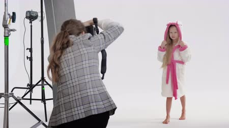 photoshoot : Unrecognizable woman taking photos of cute girl with rabbit bathrobe during photoshoot against white background
