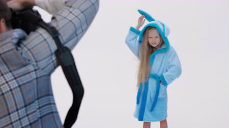 захват : Unrecognizable woman taking photos of cute girl with rabbit bathrobe during photoshoot against white background